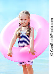 happy little girl and swim ring at the beach