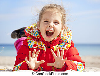 Happy little girl at the beach in spring time.