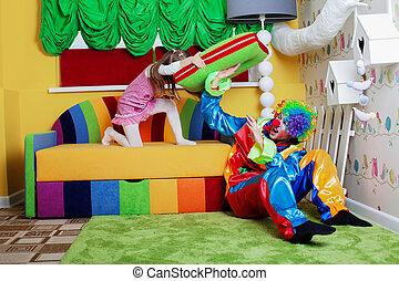 Happy little girl beats clown with a big pillow.