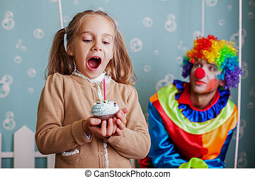 Happy little girl blows out the candle on cake.