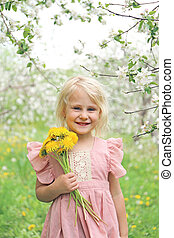 Happy Little Girl Child Holding Flowers Under the Apple Trees