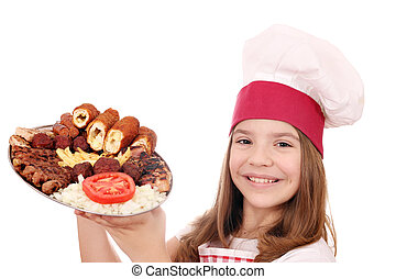 happy little girl cook holding grilled meat on plate