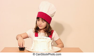 happy little girl cook with cake
