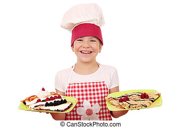 happy little girl cook with crepes on plate