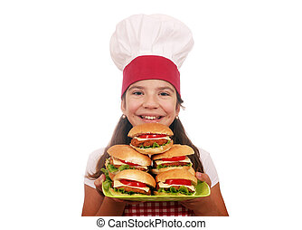 happy little girl cook with hamburgers fast food