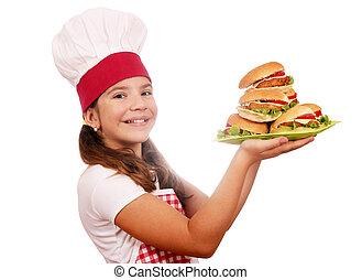 happy little girl cook with hamburgers on plate