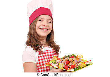 happy little girl cook with seafood on plate