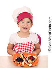 happy little girl cook with sweet crepes on plate