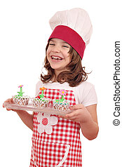 happy little girl cook with sweet muffins