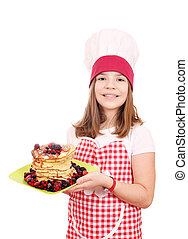 Happy little girl cook with sweet pancakes on plate