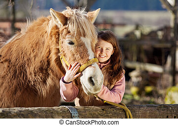Happy little girl cuddling her horse - Happy little girl...