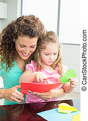 Happy little girl cutting paper shapes with mother at the table