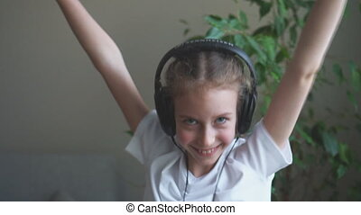 Happy little girl dancing in headphones. Slow motion.