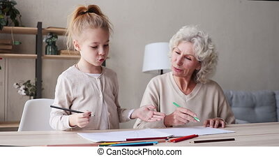 Happy little girl drawing pictures with mature grandmother.