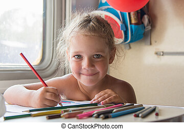 Happy little girl drawing with pencils at a table in a train