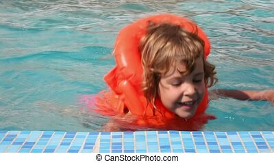 happy little girl dressed in inflatable jacket swims in pool