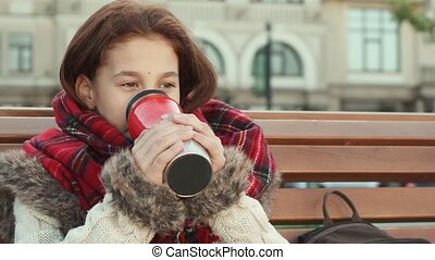Happy little girl drinks a warm drink while sitting on the street