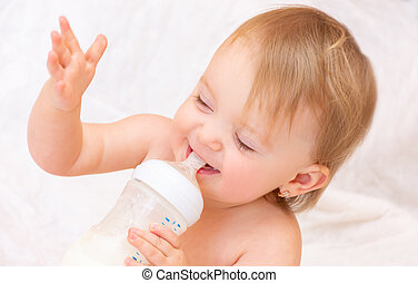 happy little girl drinks milk from a bottle. Baby food. concept of artificial feed.