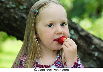 Happy little girl eating a strawberry.
