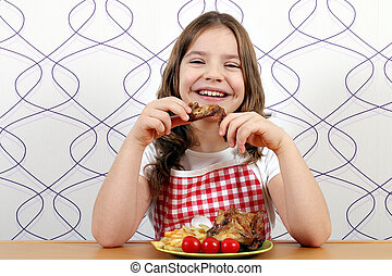 happy little girl eating chicken wings