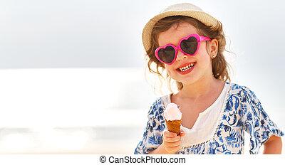 Happy little girl eating ice cream on beach