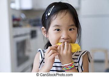 Happy little girl eating mango