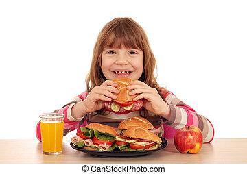 happy little girl eating sandwich