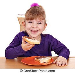little girl eats bread