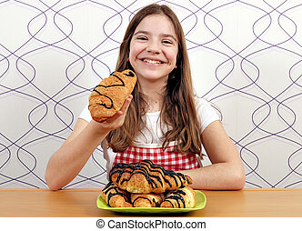 happy little girl eats croissant with chocolate