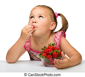 Happy little girl eats strawberries, isolated over white