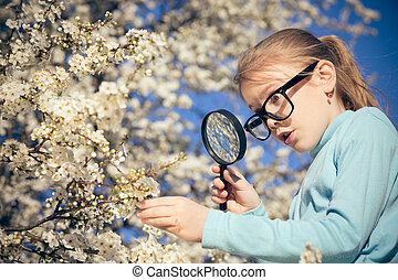 Happy little girl exploring nature with magnifying glass at the day time