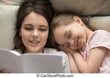 Happy little girl falling asleep in bed mum reading book