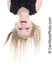 Happy little girl hanging upside down isolated on white