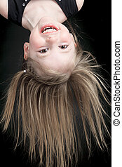 Happy little girl hanging upside down isolated on black