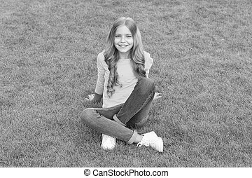 happy little girl has long curly hair. kid beauty and fashion. teen girl after hairdresser. relax on green grass. spring leisure time. happy childhood. kid with stylish hair. cheerful smile