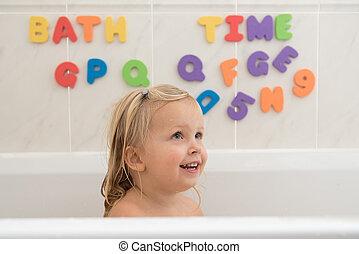 Happy little girl having a bath