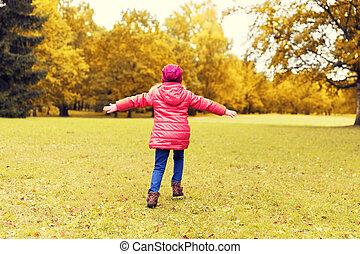 happy little girl having fun in autumn park