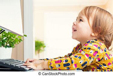 Happy little girl having fun using her computer