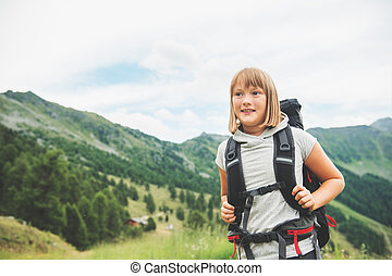 Happy little girl hiking in swiss Alps, wearing black backpack, travel with kids. Image taken in canton of Valais, Switzerland