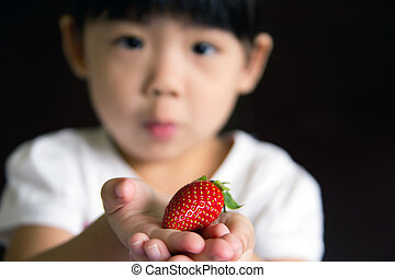 Happy little girl hold a strawberry
