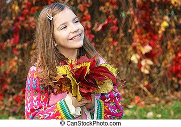 happy little girl holding autumn leaves