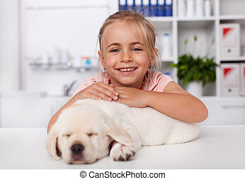 Happy little girl holding her sleeping puppy dog at the veterinary doctor office