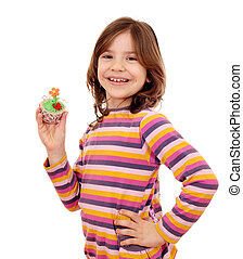 happy little girl holding spring flower muffin