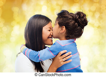 happy little girl hugging and kissing her mother - family,...