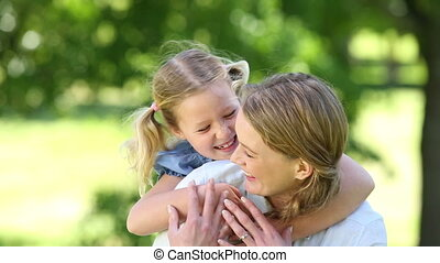 Happy little girl hugging mother in the park on a sunny day