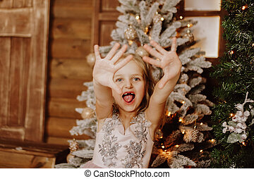 Little girl in a pink dress grimaces on the background of the Christmas tree