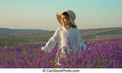 Happy little girl in a straw hat having fun in a lavender blossoming field