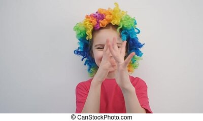 Happy little girl in colorful wig teasing while putting hands at her nose on wall background