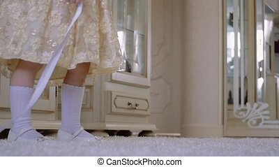 Happy little girl in dress is jumping on the floor with white ribbon.