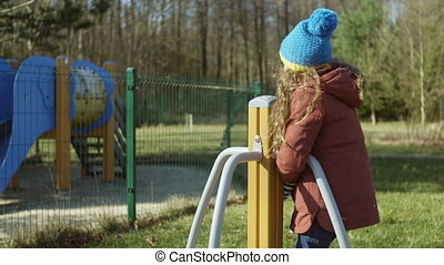 Happy little girl in good mood playing on the playground. Female turning on the carousel and smling. Carefree childhood.